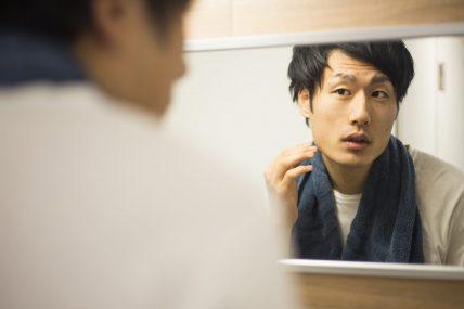 首にタオルをかけた鏡を見る男性